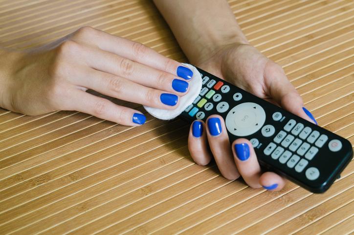 Une femme nettoyant une télécommande de télévision