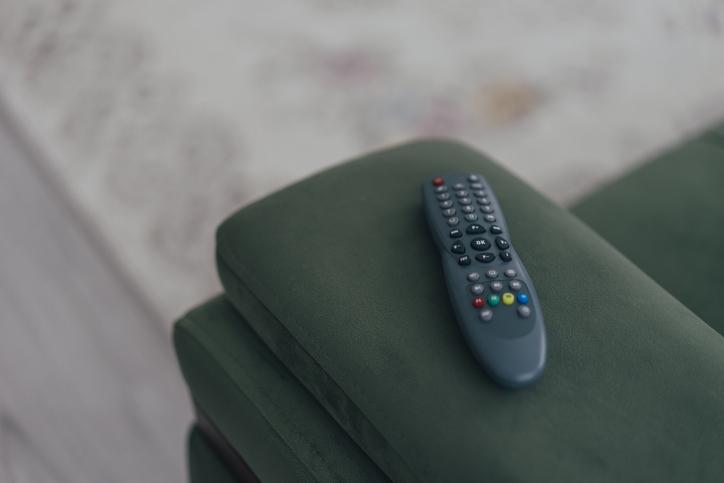 Une télécommande de téléviseur posée sur un canapé